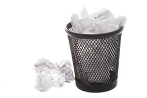Rubbish basket full of white crumpled papers